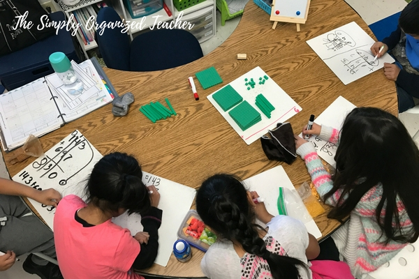 Students sitting at a table and working on small white boards. Green base ten blocks are on the table.