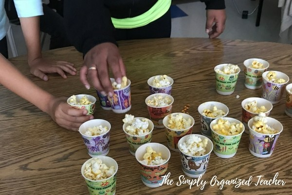 Students' hands grabbing small cups of popcorn for a classroom popcorn party.