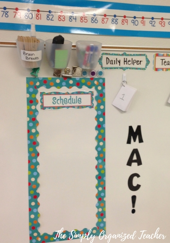 A classroom whiteboard with a daily schedule and the letters MAC cutout and pasted to the board.