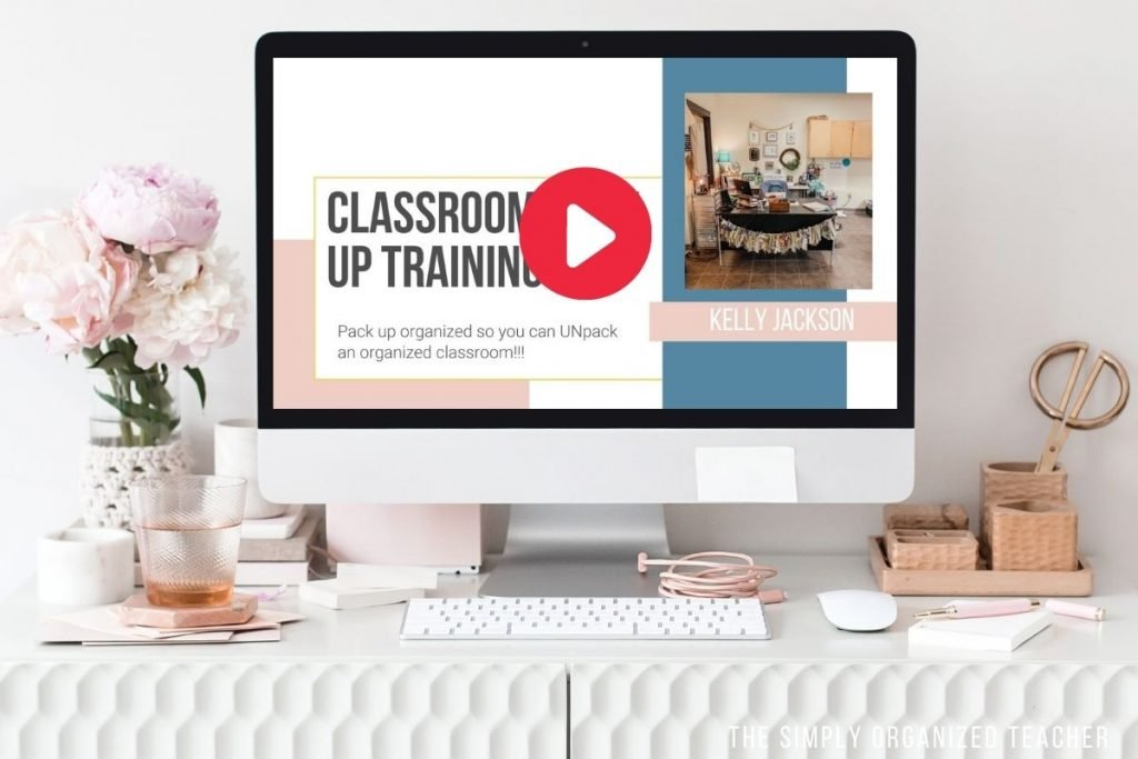 A computer sitting on a desk with a keyboard, flowers, and desk supplies surrounding the monitor. On the monitor is the Classroom Pack Up Training Video