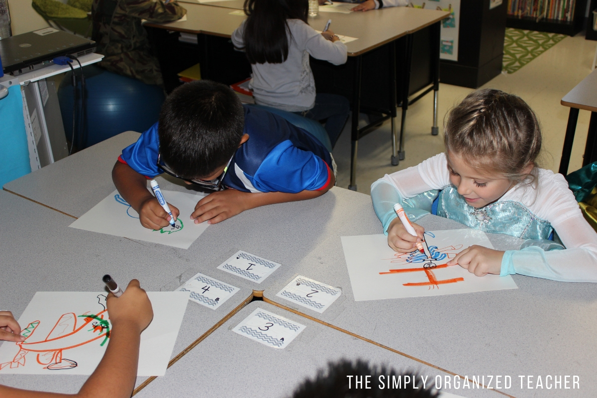 Children sitting at a desk and drawing on a piece of paper.
