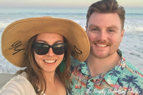 Man and woman smiling at camera with beach in the background.