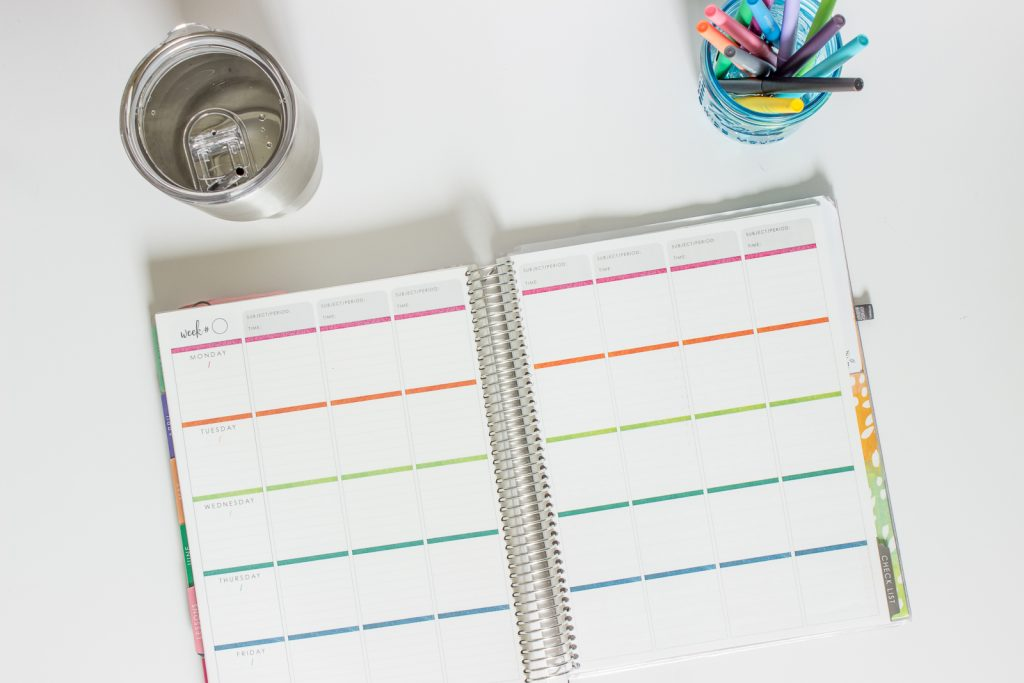 Erin Condren planner with a cup of water and jar of flair pens.