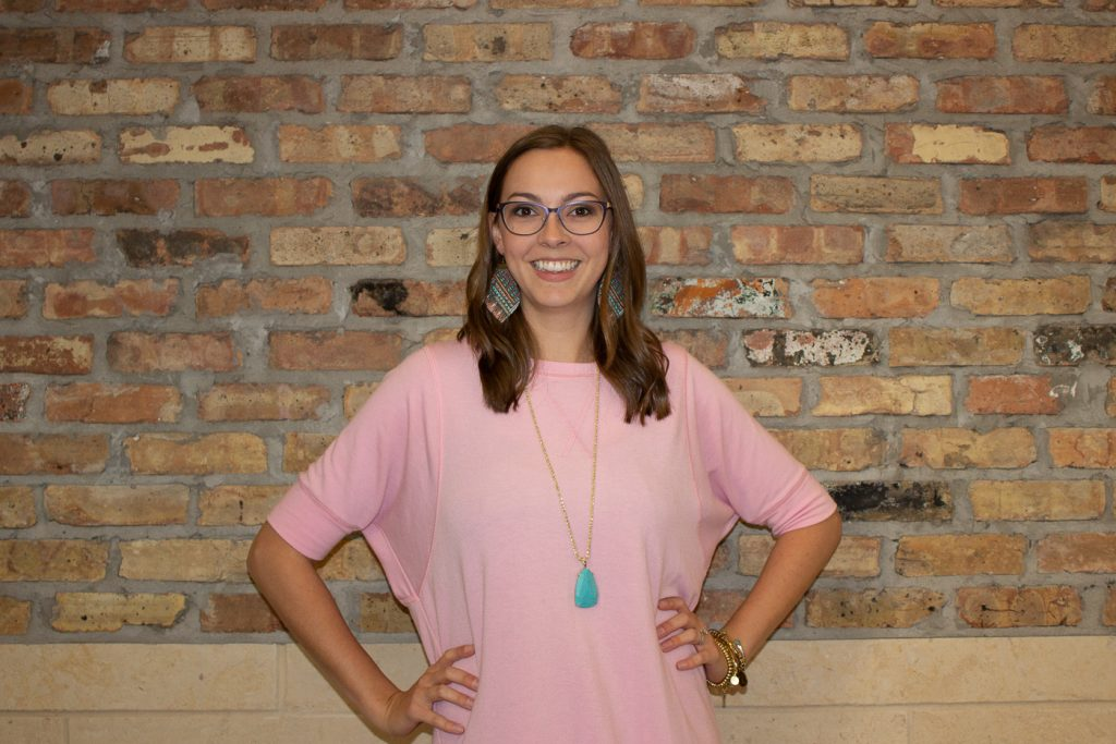 A person standing in front of a brick wall