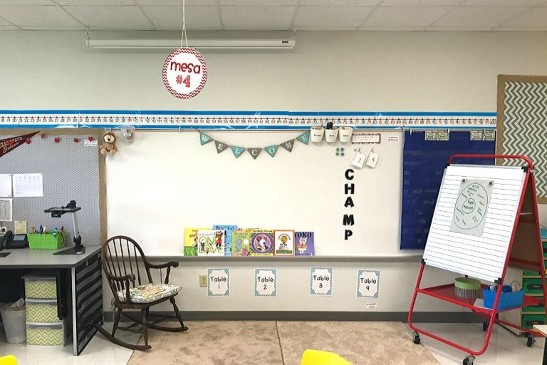 A classroom setup with a white board, easel, rocking chair, and books on the white board ledge.
