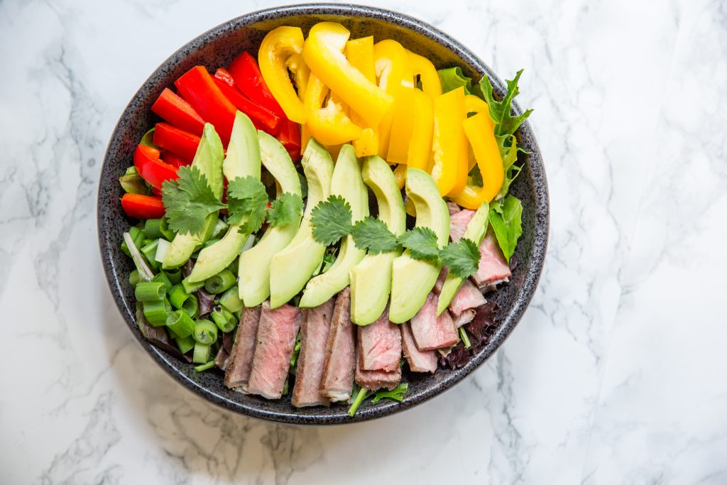 A bowl of vegetables, with Salad and Steak
