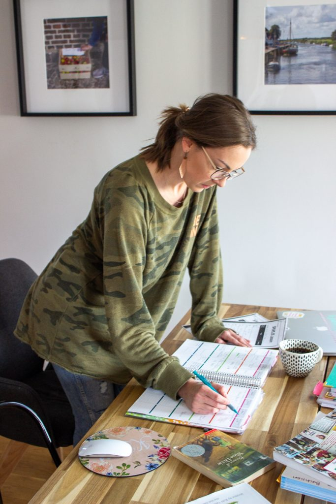 A woman sitting at a table writing in a lesson planner