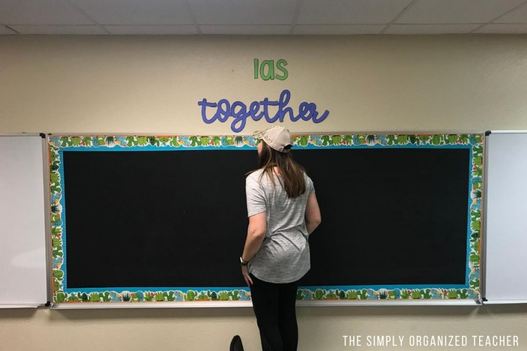 Teacher standing on chair to hang letters above whiteboard.
