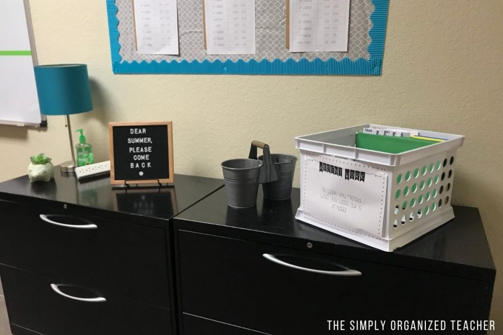 A high school classroom entrance area set up with lamp, a sign, and turn-in basket.