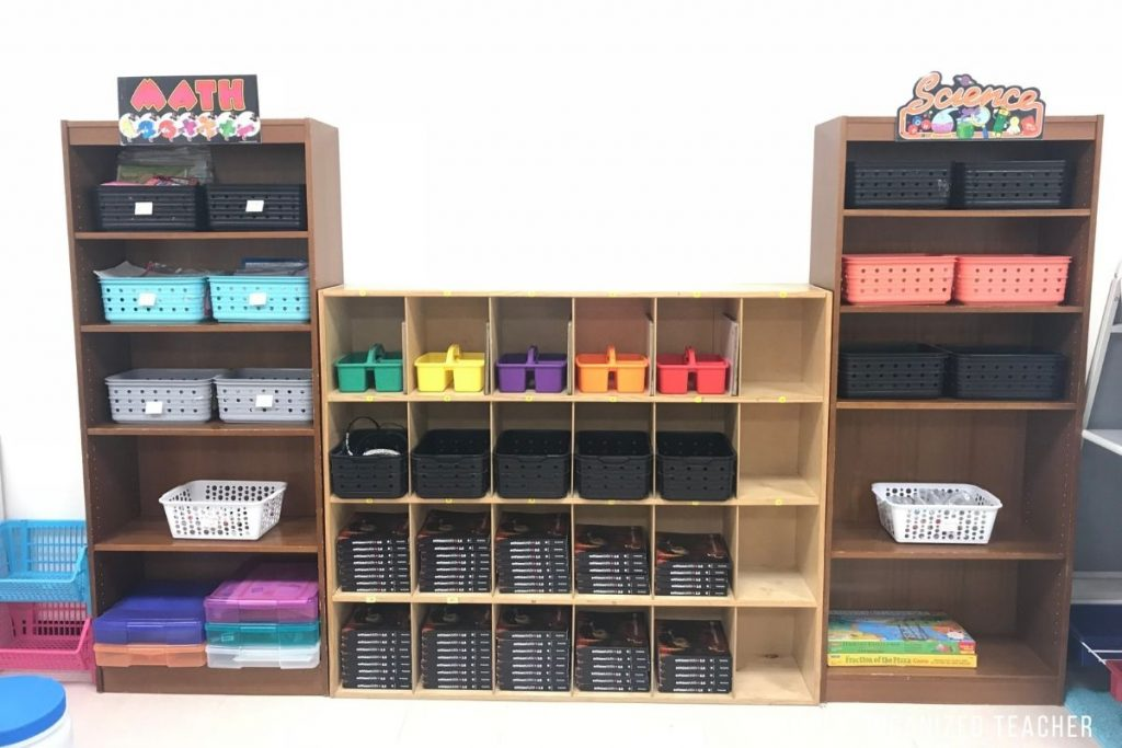 Bookshelves inside a classroom organized by subject and with similar shaped bins.