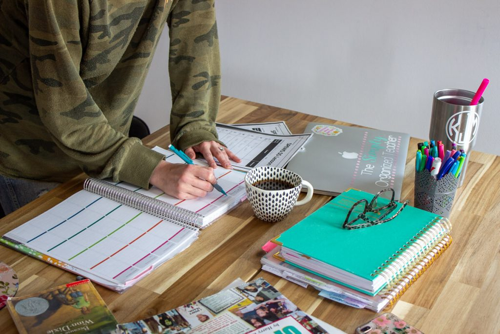 A woman writing in lesson planner on a desk.