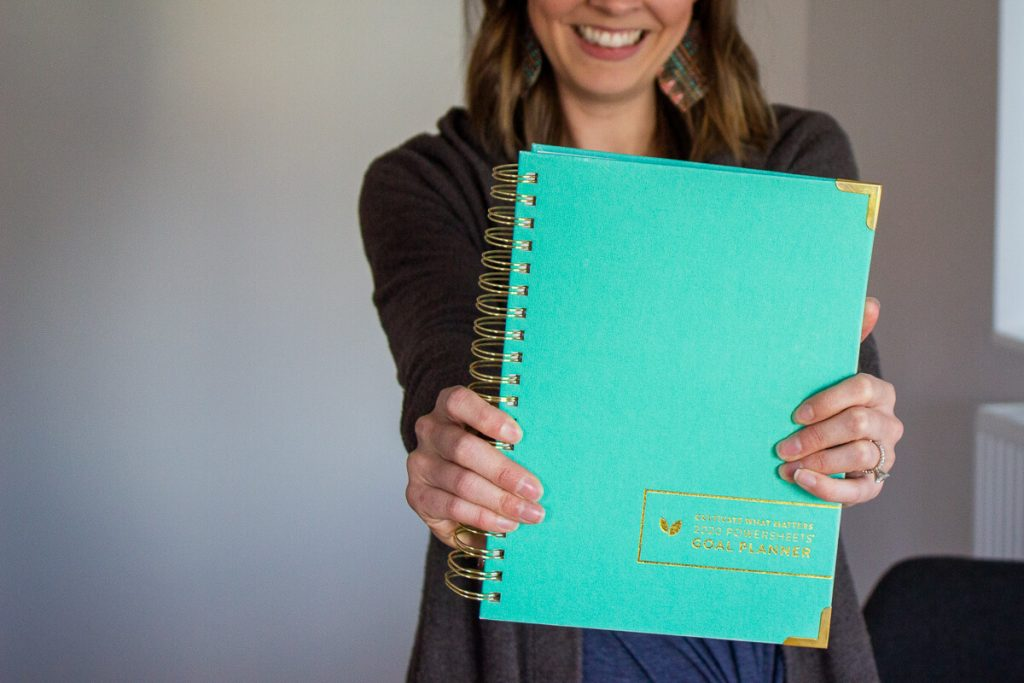 woman holding teal PowerSheets journal