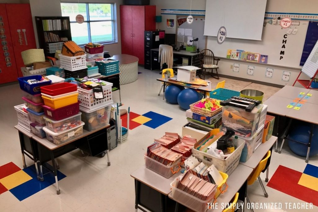 A classroom with a lot of boxes and bins on top of student desks.