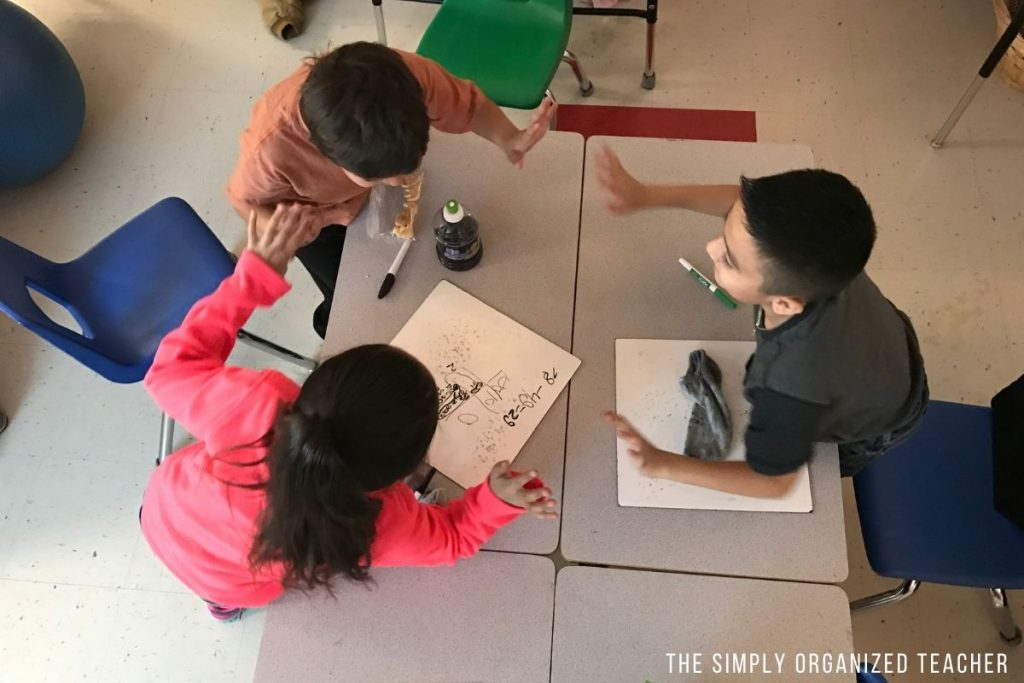Three students giving high fives around a table after completing their work.