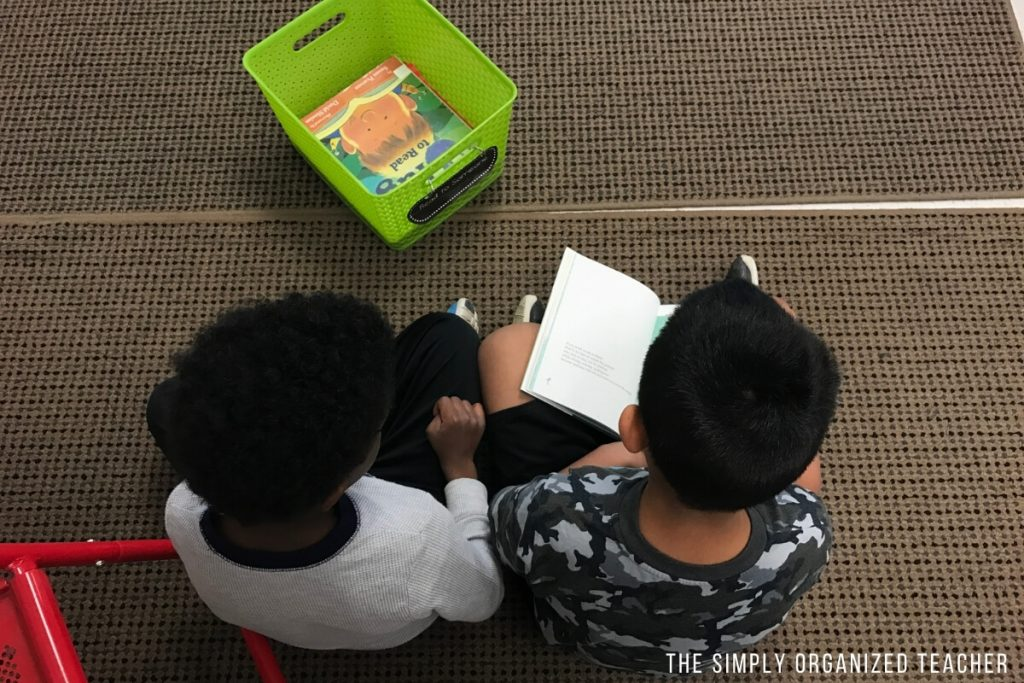Boys sitting on carpet and reading a book together.