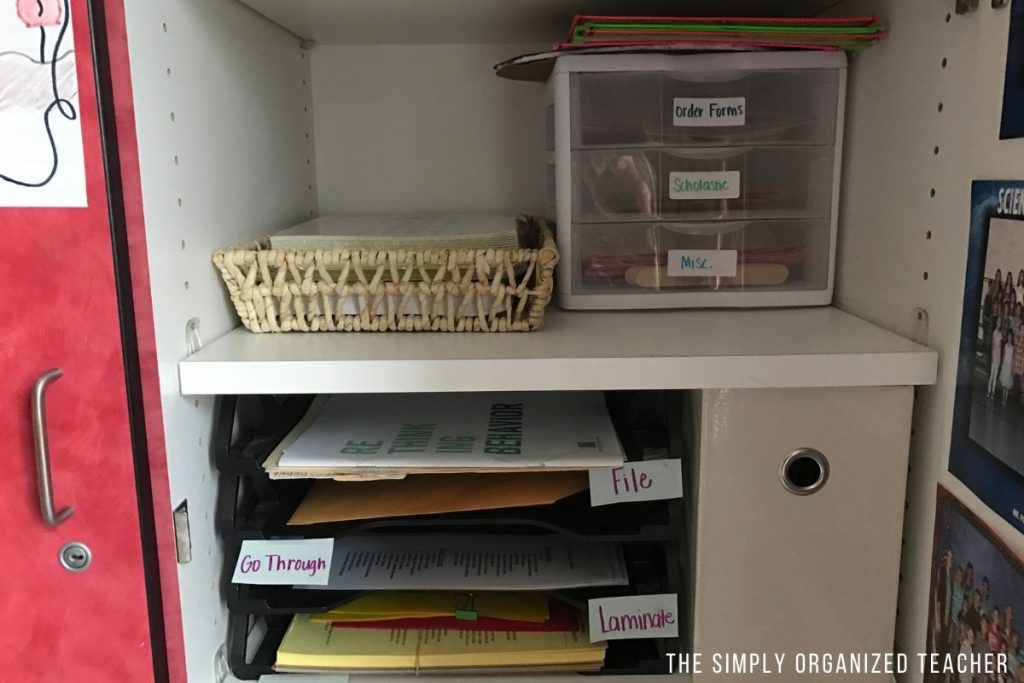 Inside classroom bookshelf with plastic drawers and plastic stackable file holders.