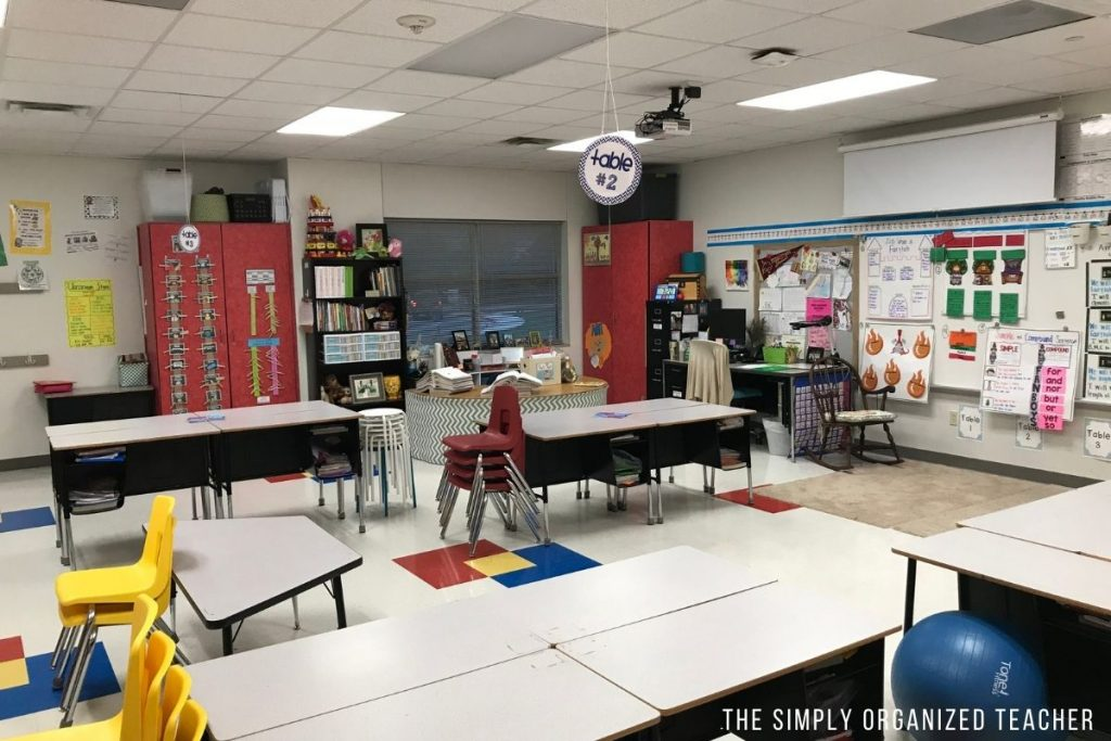 An elementary classroom with student desks and chairs stacked at the end of the tables.