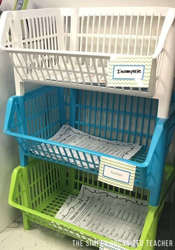 3 plastic baskets stacked and used as turn-in bins for each class.