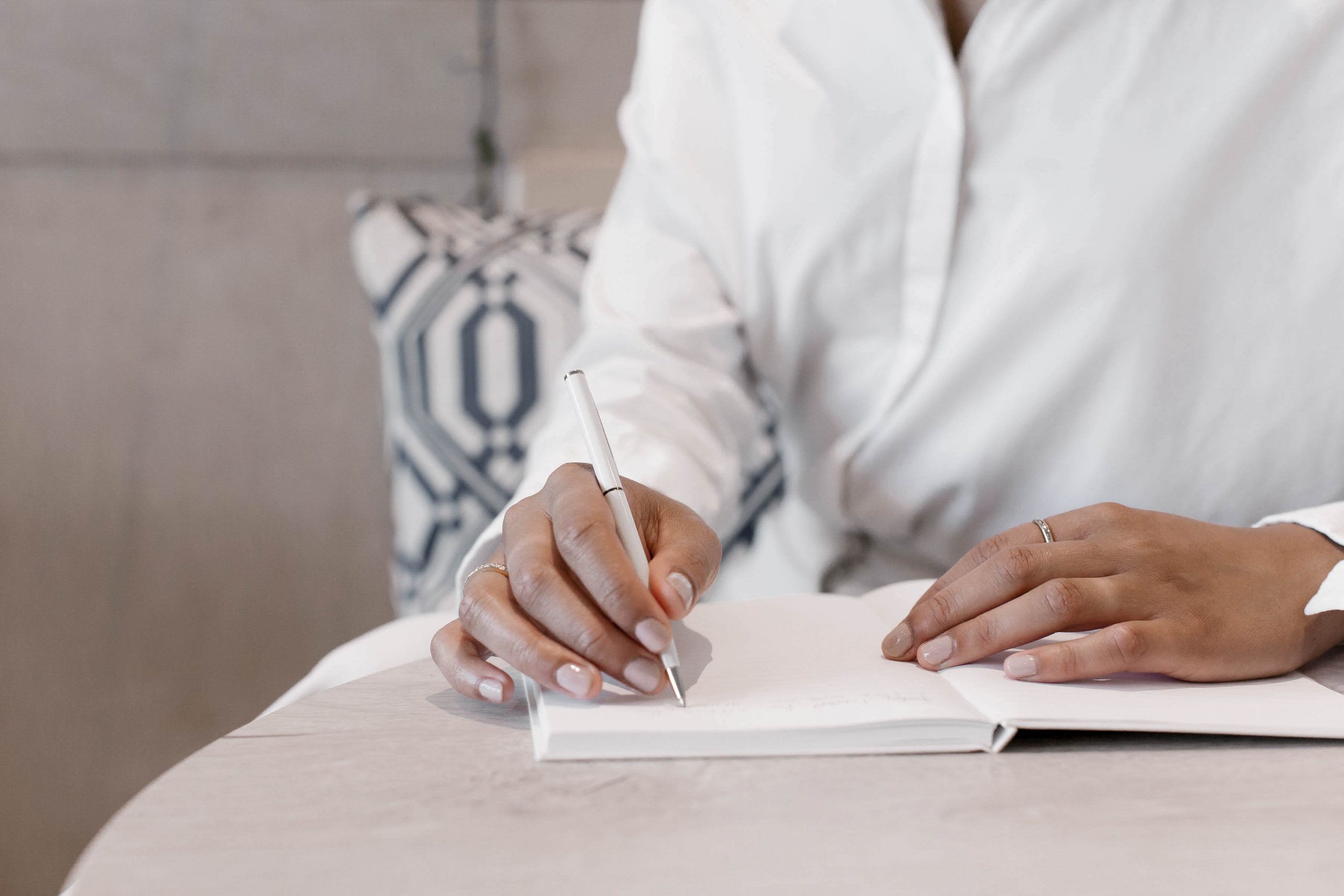 Woman's hands writing in a blank journal.