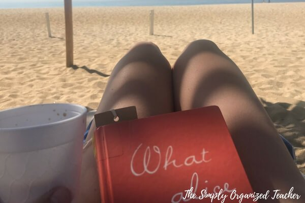 A person sitting at a beach with a book in her lap