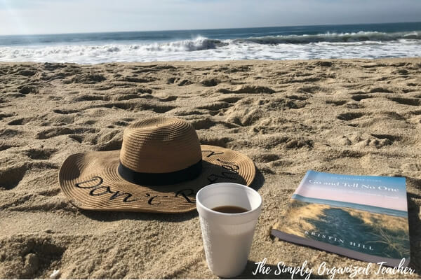 A cup of coffee sitting on top of a beach, with Vacation