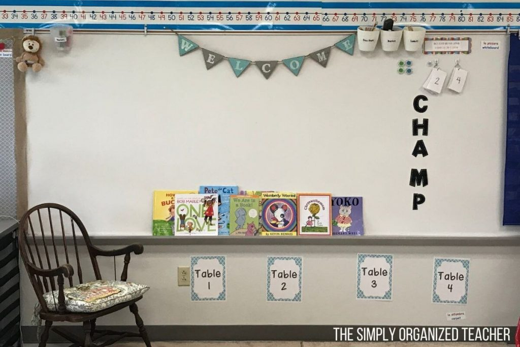 Children's books sitting on a whiteboard ledge. There is a rocking chair to the left of the white board.