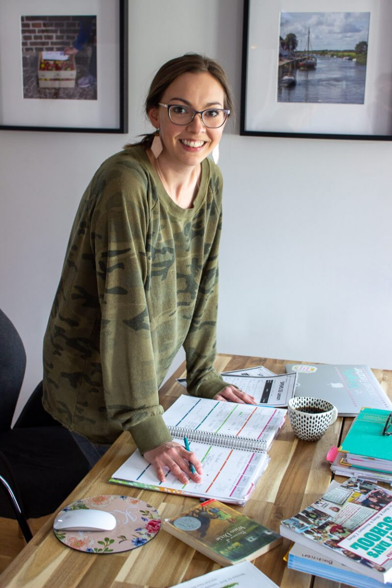 Woman smiling at camera with lesson plans, journals, and a computer on the table beneath her.