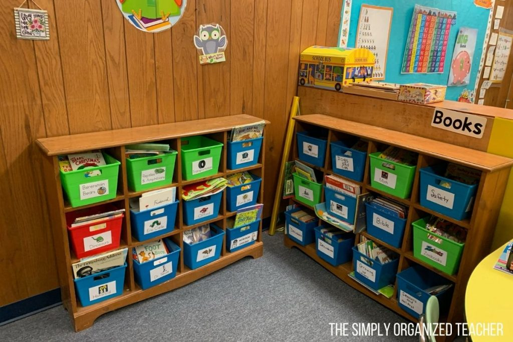 A classroom library with two bookshelves. On the shelves are green, blue, and red bins with books inside. The bins are labeled with the topic of the books inside.