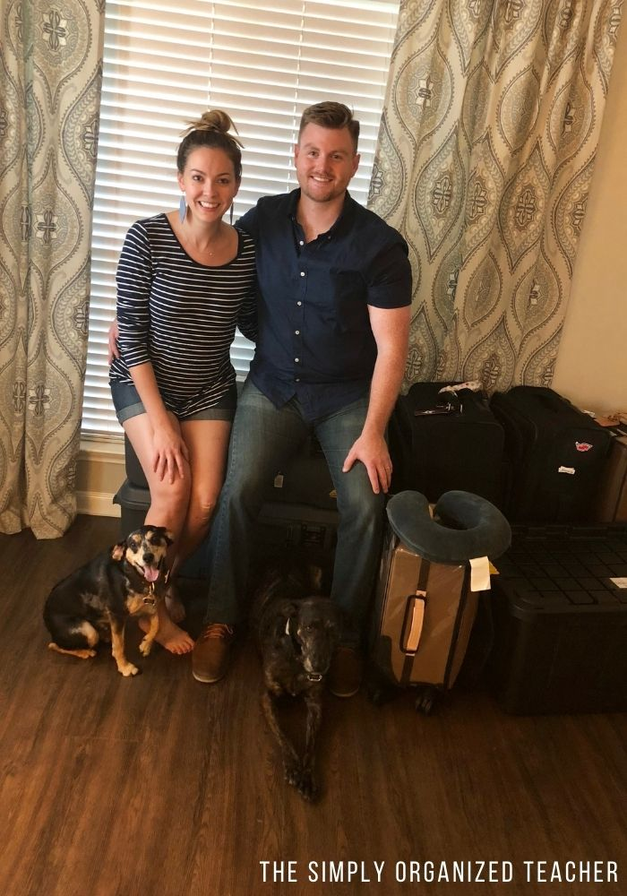 Man, woman, and two dogs sitting in front of luggage and moving boxes.
