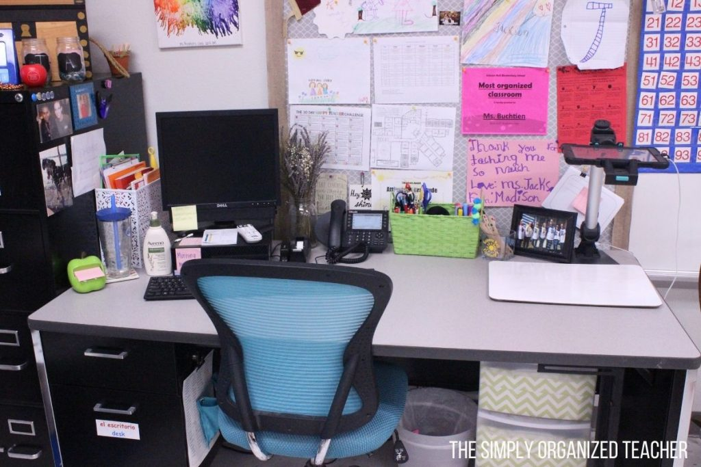 A teacher's desk with computer, phone, desk supplies, pens, and a document camera.