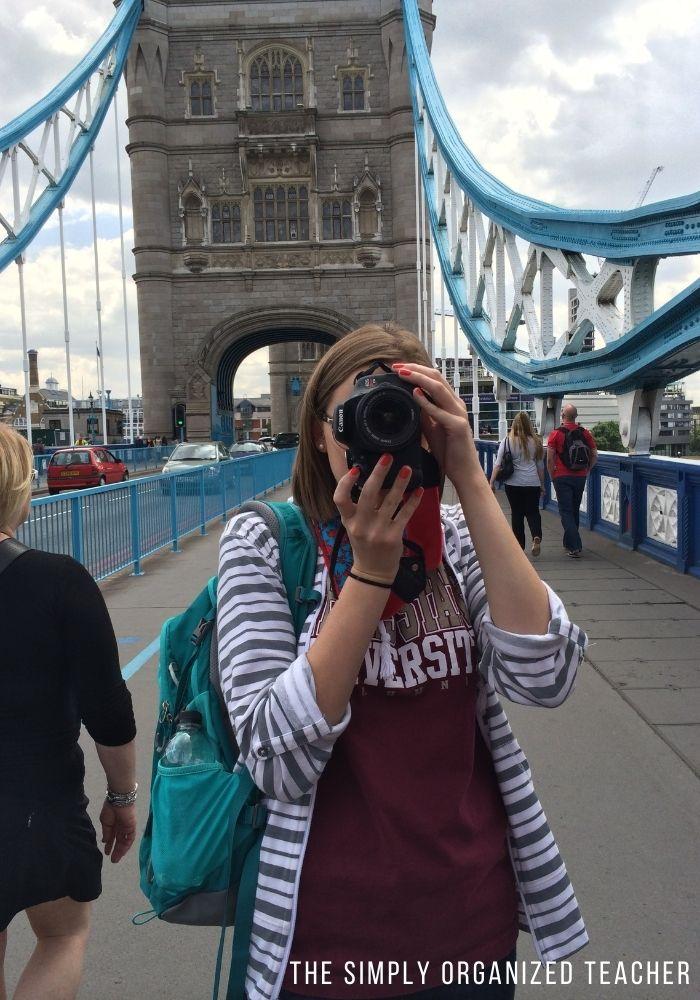 Woman looking in camera viewfinder with London Bridge behind her.