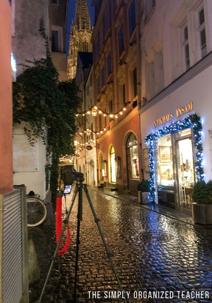 A camera on a tripod in a small alleyway looking at lights and historic buildings.