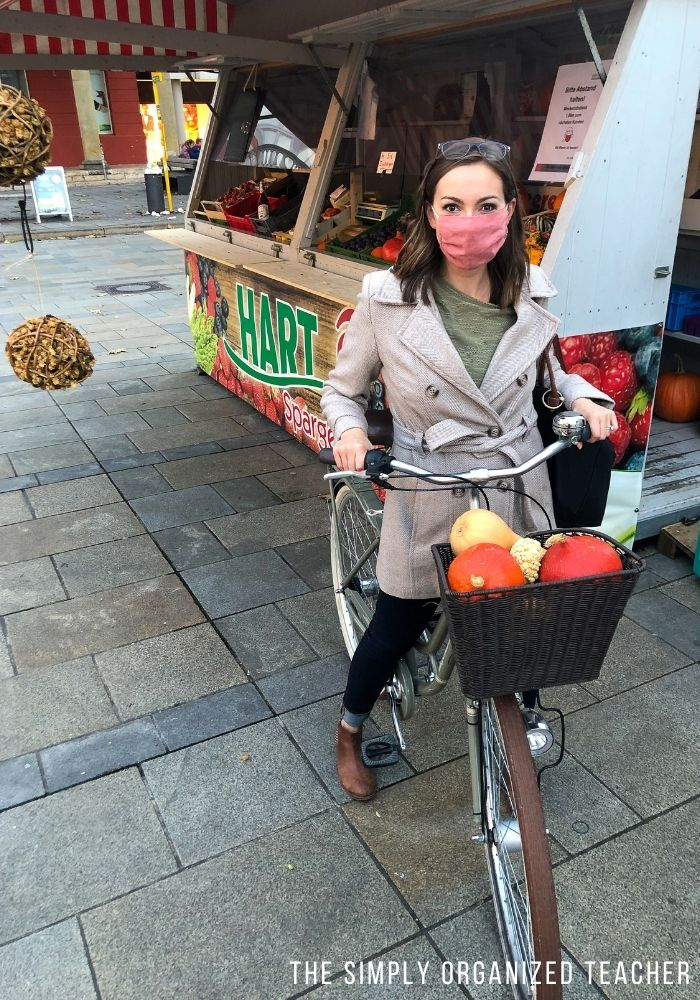 Woman on bicycle with pumpkins in the front basket.