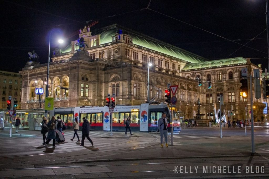 The Opera House in Vienna lit up at night with a tram driving by in front of it.