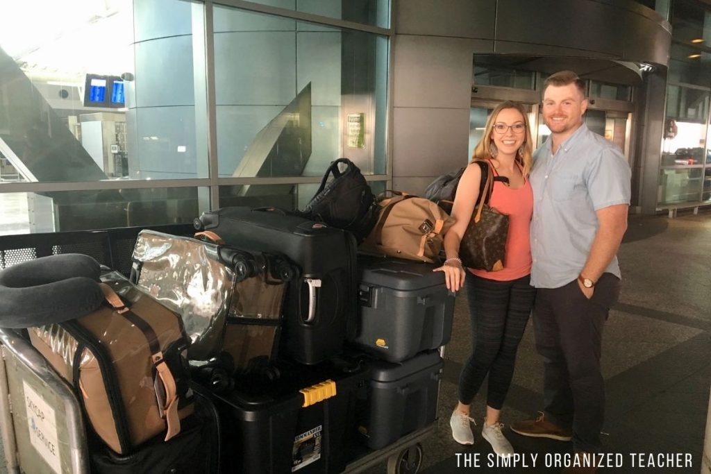 Woman and man standing in front of luggage at airport