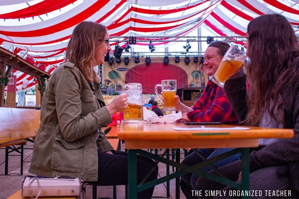 Three women sitting in a beer festival tent drinking beer and laughing.