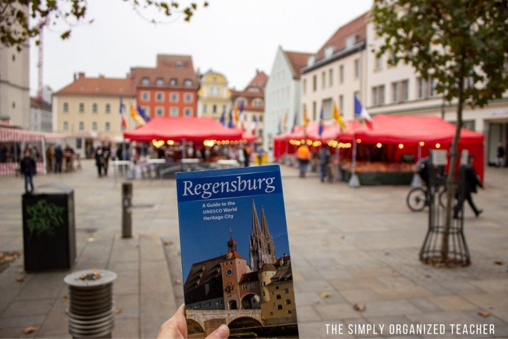 A hand holding a guidebook for Regensburg Germany with a market set up in the background.