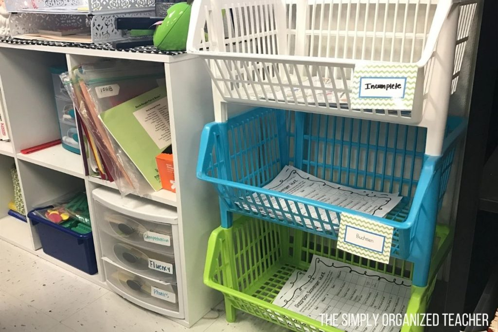 White, blue, and green baskets stacked on top of each other with papers inside.