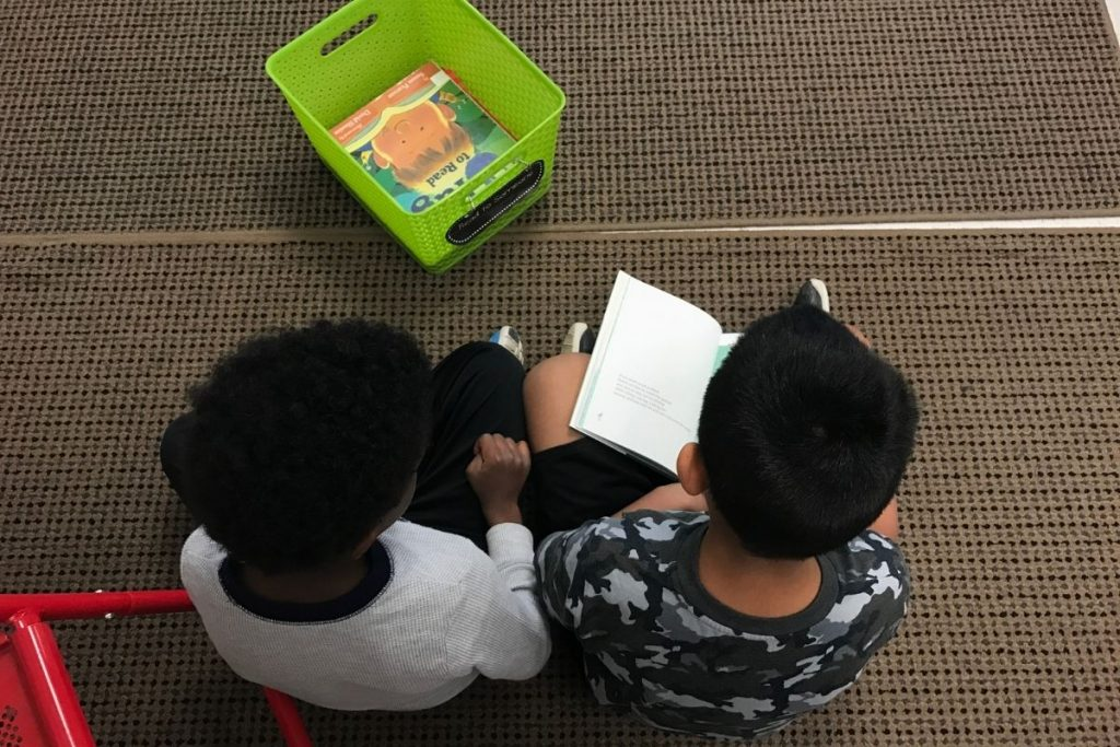 Two students sitting on a floor and reading a book together.