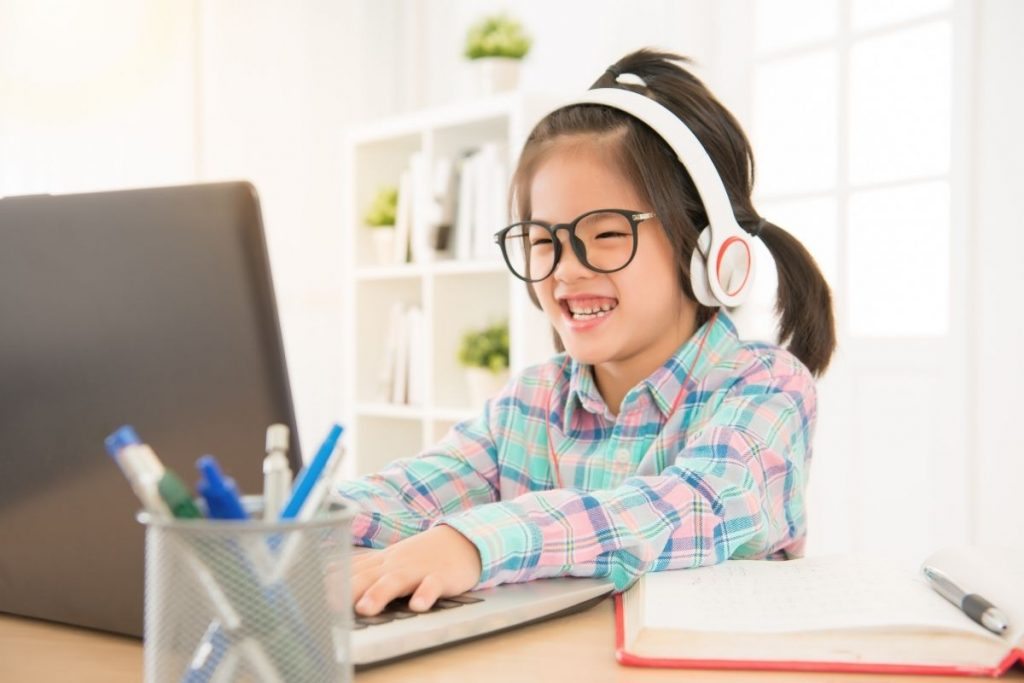 Young girl wearing headphones and working on computer. She is smiling and happy.